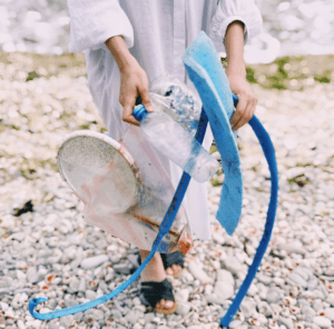 Female holding plastic waste collected on a pebbled beach