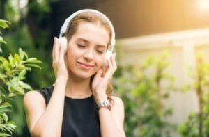 Person listening to headphones to depict listening to the 10 best nature podcasts for 2021