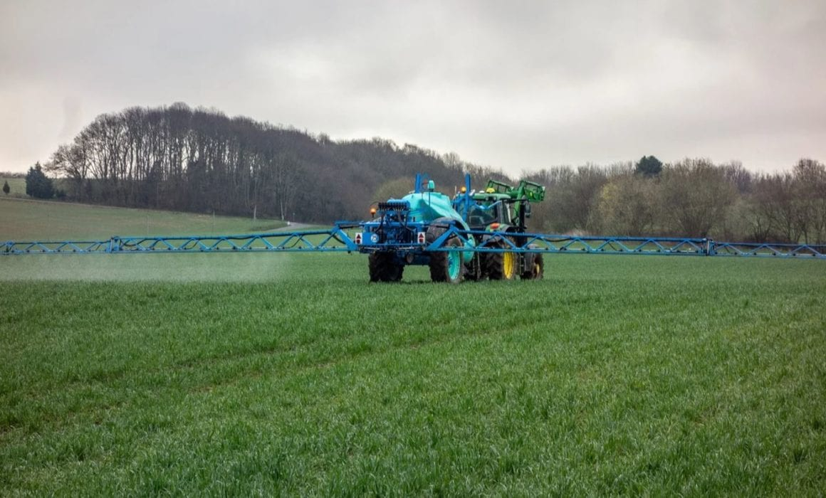 Tractor Spraying Farm Land with Pesticide